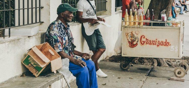 People sitting at the sidewalk in Havana
